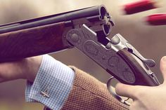 Shotgun. Never mind the gun , its just great that he is shooting in a jacket and cuff links !! Jb