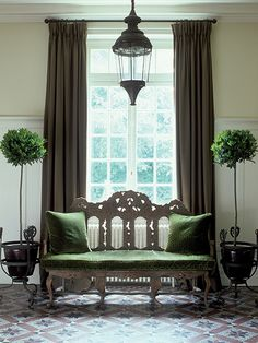 At his country home, interior designer Jean-Louis Deniot created an entry vignette comprised of a green18th-century Portuguese settee, early-18th-century wrought-iron plant stands from Spain and a mid-19th century French lantern overhead. Photo by Xavier Bejot.