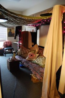 dorm style! Tapestry between two lofted beds with a couch under one bed and a tv under the other, create a nook for studying or entertaining