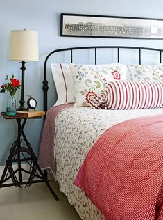 Aqua walls and red bedding bring country chic coziness to a guest bedroom. More farmhouse-style ideas: http://www.midwestliving.com/homes/decorating-ideas/fresh-farmhouse-design-ideas/?page=9