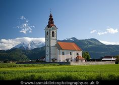 Morning light illuminating the church of saint John, Brnik, near the Ljubljana airport, Slovenia. The Kamnik Alps are in the background. The Alps have a fresh Spring coating of snow. Krvavec ski resort can also be seen in the distance behind the church. Buy a canvas print here: