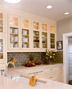 Using glass front cabinets as to frame dishes & decor in the kitchen.