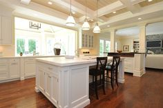source: Jillian Klaff Homes  Traditional kitchen opens into family room with Restoration Hardware keynes Single Prism pendants, coffered ceiling, white kitchen cabinets & kitchen island with marble countertops and hardwood floors.