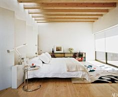 At former art director Charles Churchwood's Santa Fe, New Mexico, retreat, the master bedroom is furnished with an Eileen Gray side table from Design Within Reach, Tizio lamps by Artemide, an Yves Delorme alpaca blanket, and an Edward Fields carpet; a Steven Klein photograph is propped on the bookcase   archdigest.com