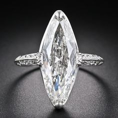 A sparkling and streamlined, early twentieth-century vintage marquise diamond, weighing just two points shy of four carats and measuring 7/8 inch long (!) (about the length of a regular cut 7.00 carat marquise) is presented in an elegantly understated platinum and diamond mounting - circa 1920s-1930s - by none other than Cartier.