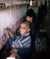 Srinagar Carpet Pictures   Young Children Weaving Carpets in Kashmir.  One light bulb hanging from the ceiling