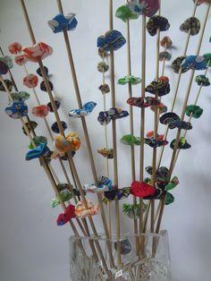 Haste de bambu com flores de fuxico com 80cm de comprimento. <br> <br>O valor informado é referente a uma única haste. <br> <br>Cada haste tem uma cor predominante, na hora da compra o comprador pode informar a cor predominante desejada. <br> <br>O vaso não está incluso.