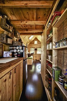LOVE the dramatic change of color on the floor - from the rest of the wood. Plus - loving those shallow shelves. Now...what keeps them on the shelves during travel, eh?    Tiny house kitchen.