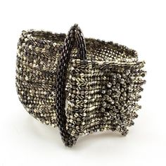 Try your hand at this absolutely beautiful statement bracelet! It is made using flat herringbone and peyote stitches. Increases and decreases in the herringbone give the bracelet a gathered look. Tumb
