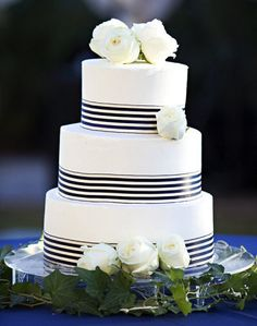 The cake will have navy and white stripe ribbon with scattered clusters of ivory spray roses and bits of greenery
