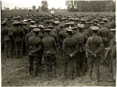 Attending church. A large group of soldiers attend a church service in a field. The priest can be seen in the middle of the picture towards the back.