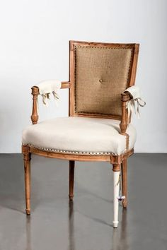 Bunakara   Bunakara Fingerprint Pure Chair   Crafted with acacia wood, the Pure Chair is upholstered with natural linen burlap and ivory linen on the seat and tie-on arm pads. Other details include spit tack trim, a single button on the inside back, a burlap twine bow and a small embellished gold nail.