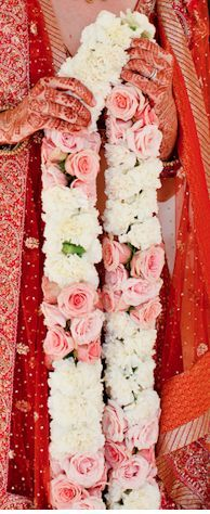 Love this white and pale pink varmala design | large chunky bright flowers pairs well with the deep red lehenga shade | Varmala Designs | Jaimala Ideas | Indian Wedding Ideas | Credits: Saved by - EMT Design | Every Indian bride's Fav. Wedding E-magazine to read. Here for any marriage advice you need | www.wittyvows.com shares things no one tells brides, covers real weddings, ideas, inspirations, design trends and the right vendors, candid photographers etc.