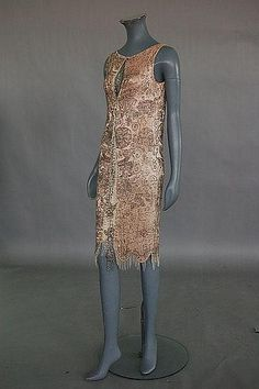 Description: A pale pink satin flapper dress, circa 1925, covered in silver bugle beads. Front