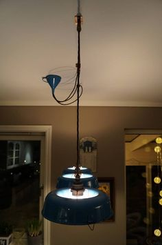 Pendant shades upcycled from cake tins in blue enamelware from the 50's. The funnel in the ceiling hiding the electrical connections is also blue enamel.