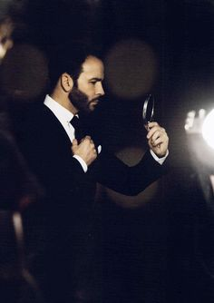 TOM FORD adjusting his tie in a hand-mirror.