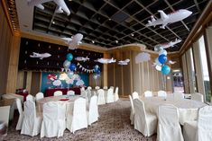 Rubber inflatable planes and paper clouds hung from the ceiling, with blue helium balloon centerpieces for Airplane birthday party by Victoria Chow