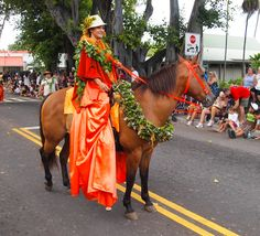 A pa'u rider in Kailua-Kona's Kamehameha Day Parade on the Big Island dressed in orange, the color representing the island of Lana'i...