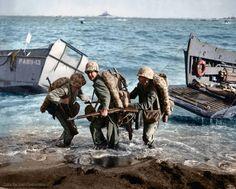 Within range of enemy fire, US Marines haul an ammunition cart up onto the beach at Iwo Jima, February 19 1945.