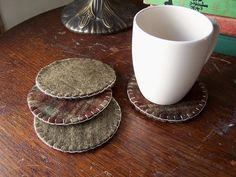 This listing is a set of four reversible coasters made from recycled wool felt. One side is a dark plaid. I like to call it woodsy, because the colors