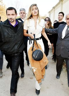 Gigi Hadid pairs a jumpsuit with a suede bomber jacket, a circle cross-body bag and a black belt.
