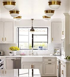 Sometimes more IS more: a gaggle of brass ceiling fixtures and complementary hardware add plenty of sizzle to a small and previously spare white kitchen. Cabinets and walls in White Opulence; ceiling in Decorators White. Image: eleanorbusing.com