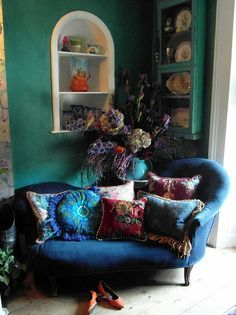 Blue couch, warm and cool color pillows, turquoise walls with white accents.