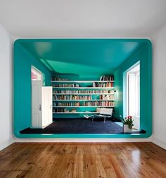Blue mini library and on the other side of the room (wooden floor section) will be a perfect place for a study room.
