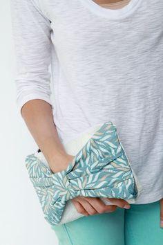 Cartera o bolso de mano con aplicación lazada para poder agarrarlo y lucirlo
