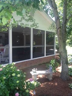 Oak Ridge NC screen porch viewed from the outside with brick foundation and white metal wrapped posts.