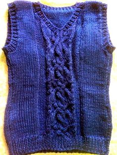 Fancy cross and cable school vest for girls in navy blue.  This pattern can be made for boy as well if eliminate the body shaping. This vest pattern is free.