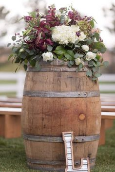 Outdoor wedding ceremony decor idea - whiskey barrels with purple + white flowers and greenery arrangement {Irving Photography}
