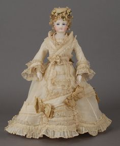 French bisque fashion doll, ca 1875, wears a cream gauze dress with delicate ruching, pleating and overall exquisite lines. Over scale camel satin bows decorate the entire dress, while a chapeau of camel flannel with floral decoration blends beautifully with the ensemble.