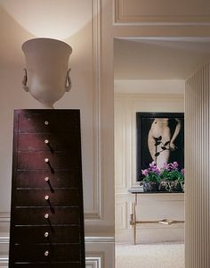An urn lamp is atop a chest by Pheasant, who designed the majority of the furnishings in the apartment. In the hall, Eve, a 1977 photograph by Colby Caldwell, hangs above an Agostini table.  Photography by Durston Saylor/Before Photography Courtesy Thomas Pheasant, Inc.