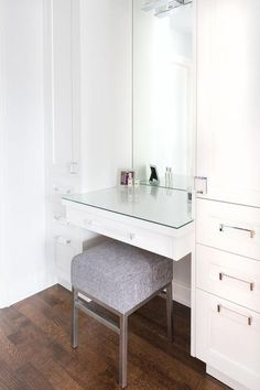 Chic dressing room boasts a built in make up vanity with mirrored top paired with a gray stool flanked by floor to ceiling cabinets.
