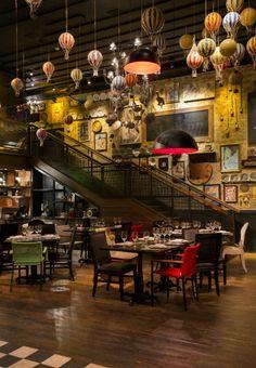 Detalhes na decoração: mistura de piso, luminárias e objetos decorativos no teto, com uma mistura de mesas e cadeiras.