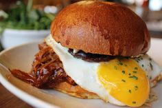 """Duck confit """"sloppy joe"""" with smoked ricotta, fried egg, truffle, red wine onions, baby greens"""