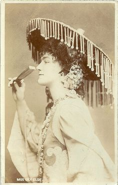 Miss Lily Elsie  Elsie (1886-1962) basically was an Edwardian music hall singer and actress, who conquered British audiences overnight in 1907 with her role in The Merry Widow, but she also performed in two films: The Great Love (1918) by D.W. Griffith and the British film Comradeship (Maurice Elvey 1919). The card above must refer to A Chinese Honeymoon (1903)