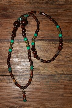 Necklace with brown, green-turquoise & khaki wood beads, coconut shell rondelles, bronze spacer beads, brown glass beads & Amazonite Chips. 20 €
