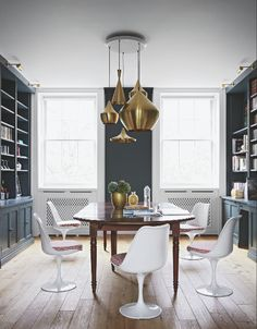 This regency room is modernised with modern white dining chairs and iconic metal pendant lights in a cluster. Image : Livingetc