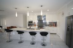 Gloss vinyl kitchen with stone bench tops.