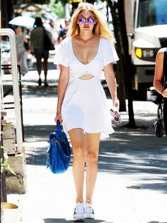 A white dress with a cutout is paired with tennis shoes, reflective sunglasses and blue bag.