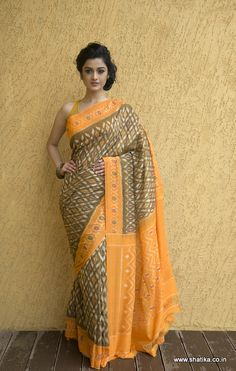 Classic is how we term this elegant Pochampally saree. The faded olive green saree with traditional white geometric prints with ikat dyes contrast strikingly with the yellow pallu and border. The charming zig zag patterns on the pallu contrast with the blurry designs on the body of this six yards of loveliness. Shop this stylish yet traditional Devpriyaa Double Ikat Pochampally Cotton Saree to be favorite of your own.