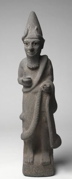 Priest-King or Deity.Hittite,North Syria,early 17th Century BC.The Hittites migrated into Anatolia in the 3rd millennium bc.From about 1600-1200 bc their empire was at its peak. This large basalt sculpture is exceptionally rare in depicting a Hittite god or priest-king wearing a horned conical crown, false beard, and long robe. He holds a bowl in his right hand and once held something in his left, perhaps a staff or sword.