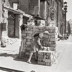 A woman neatly stacking stones in Berlin, photographed by Ernst Hahn (1950)