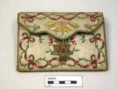 This is a lovely example from between 1750 - 1790. Envelope style it is made from stiffened, figured white silk embroidered on both sides with twined ribbons, flowers, butterfly, basket of flowers, flowering tree and bird. It too measures about 6 inches wide and 4 inches deep (approx. 16cm x 11cm).
