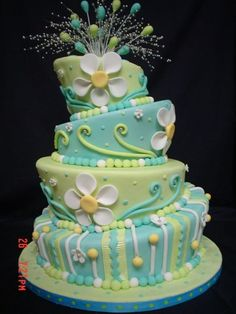 A very prettily decorated and coloured topsy turvy cake. I love the green swirls.