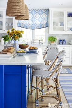 "ELECTRIC BLUE – ""Cobalt was a fun way to steer clear of the typical all-white kitchen,"" says Mark D. Sikes, who chose Farrow & Ball's Stiffkey Blue for this cheery island; the stools are by Serena & Lily, the Roman shade is in a China Seas fabric and the rugs are from Dash & Albert. Click through for more kitchen design ideas."