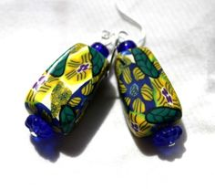 Jungle flowers hidden amongst the foliage, that's what these hand crafted earrings remind me of.  Deep blues, yellows, and greens fairly leap off the handmade polymer clay beads that make up these ear