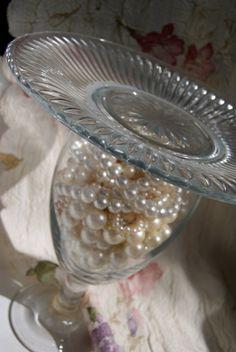 Prato de bolo de vidro com a vasilha de vidro com pérolas azuis dentro pra colocar docinho na mesa